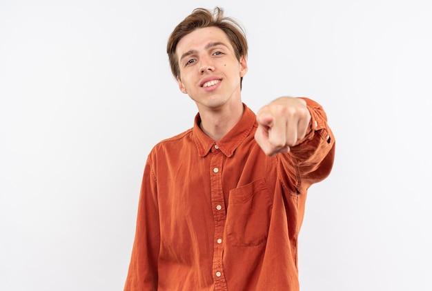 Glimlachende jonge knappe man met een rood shirt wijst naar de camera