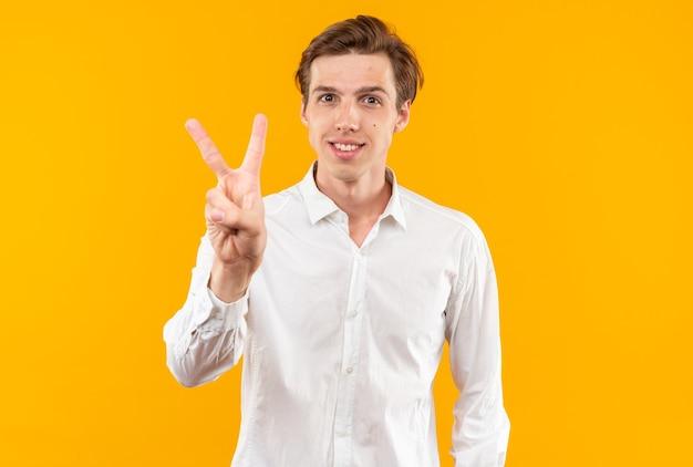 Glimlachende jonge knappe man met een wit overhemd met twee geïsoleerd op een oranje muur