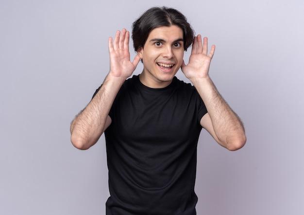 Glimlachende jonge knappe man met een zwart t-shirt, hand in hand rond de oren, geïsoleerd op een witte muur