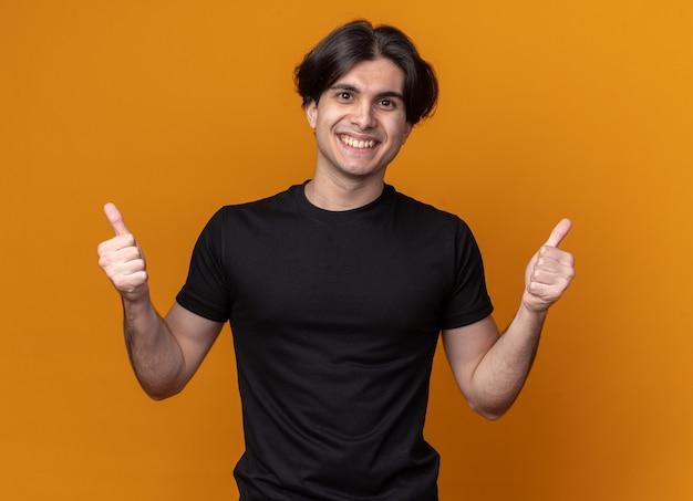 Glimlachende jonge knappe man met een zwart t-shirt met duimen omhoog geïsoleerd op een oranje muur