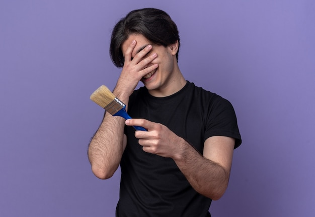 Glimlachende jonge knappe man met een zwart t-shirt met een met verfkwast bedekt gezicht en een hand geïsoleerd op een paarse muur
