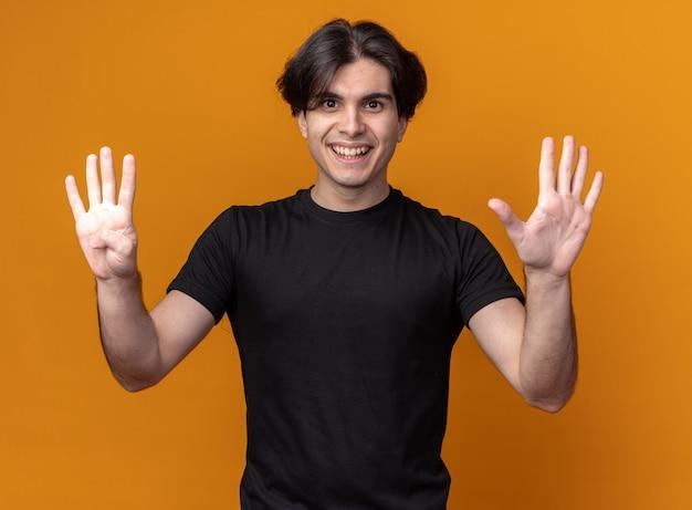 Glimlachende jonge knappe man met een zwart t-shirt met verschillende nummers geïsoleerd op een oranje muur