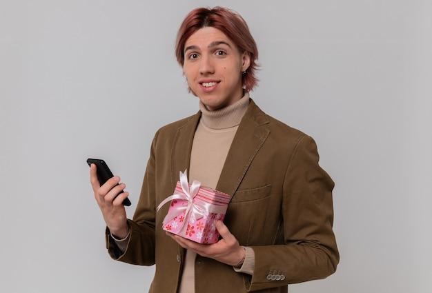 Glimlachende jonge knappe man met geschenkdoos en telefoon