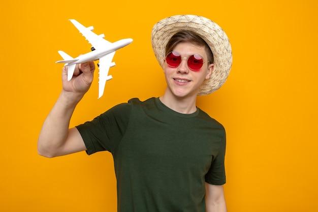 Glimlachende jonge knappe man met hoed met bril met speelgoedvliegtuig geïsoleerd op oranje muur