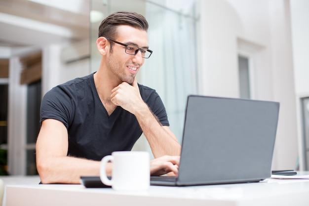Glimlachende jonge knappe man werken op laptop