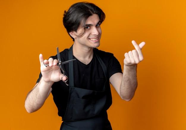 Glimlachende jonge knappe mannelijke kapper in eenvormige holdingsschaar en het tonen van uiteindegebaar dat op oranje wordt geïsoleerd