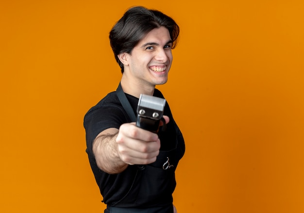 Glimlachende jonge knappe mannelijke kapper in uniform stak tondeuses op camera geïsoleerd op een oranje achtergrond
