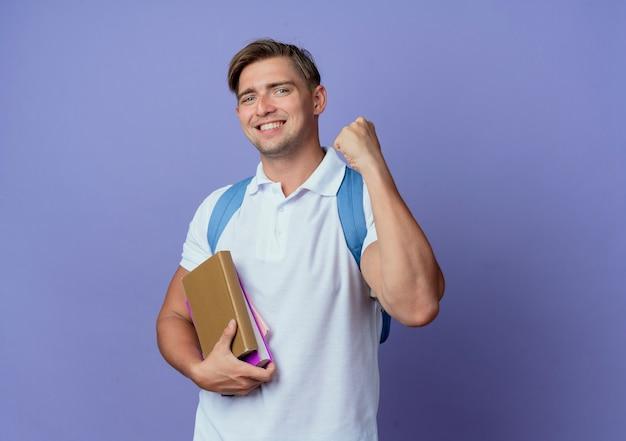 Glimlachende jonge knappe mannelijke student die de boeken van de achterzakholding draagt en ja gebaar toont dat op blauw wordt geïsoleerd
