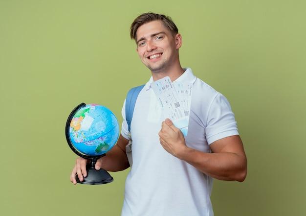 Glimlachende jonge knappe mannelijke student die de kaartjes van de achterzakholding en bol draagt die op groene olijf wordt geïsoleerd