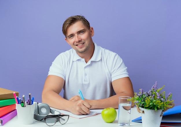 Glimlachende jonge knappe mannelijke studentenzitting bij bureau met schoolhulpmiddelen die iets op notitieboekje schrijven dat op blauw wordt geïsoleerd