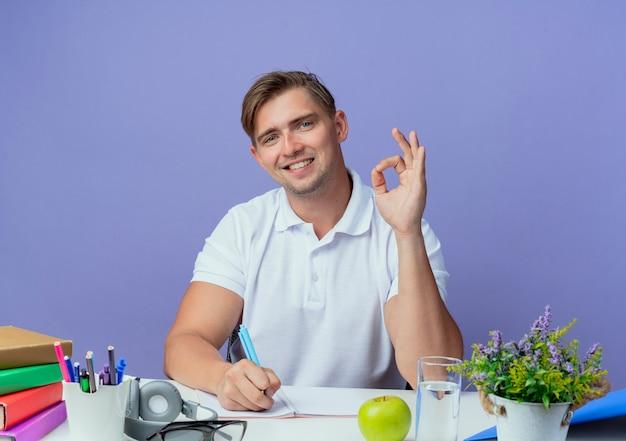 Glimlachende jonge knappe mannelijke studentenzitting bij bureau met schoolhulpmiddelen die ok gebaar tonen en iets schrijven op notitieboekje dat op blauw wordt geïsoleerd