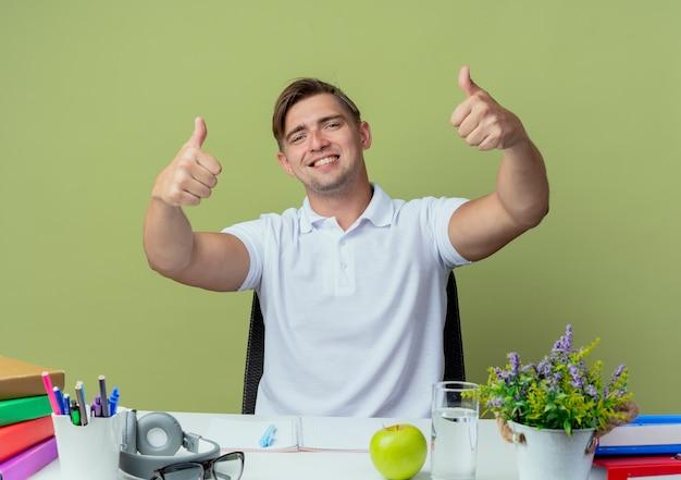 Glimlachende jonge knappe mannelijke studentenzitting bij bureau met schoolhulpmiddelen zijn duimen omhoog geïsoleerd op olijfgroen