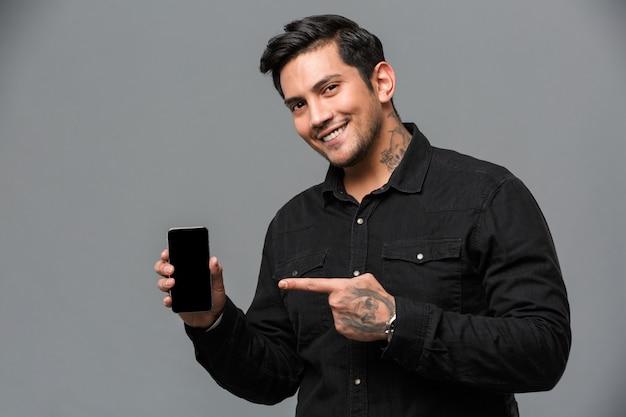 Glimlachende jonge knappe mens die aan vertoning van mobiele telefoon richt.