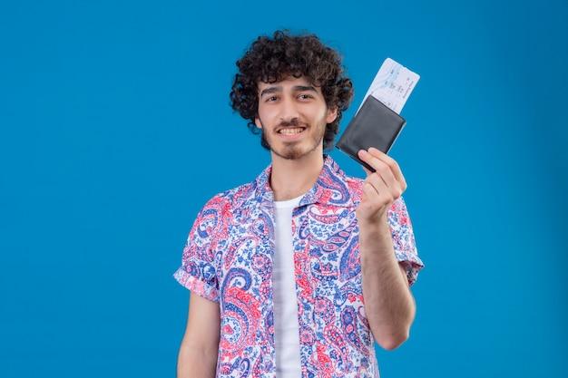 Glimlachende jonge knappe reizigersmens die portefeuille en vliegtuigkaartjes toont op geïsoleerde blauwe muur met exemplaarruimte