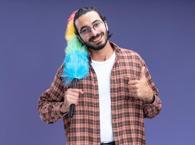 Glimlachende jonge knappe schoonmaakster die de plumeau van de t-shirtholding op schouder draagt en duim toont die omhoog op blauwe muur wordt geïsoleerd