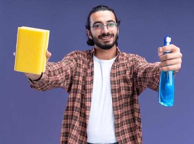 Glimlachende jonge knappe schoonmaakster die t-shirt draagt die nevelfles met spons aan voorzijde houdt die op blauwe muur wordt geïsoleerd