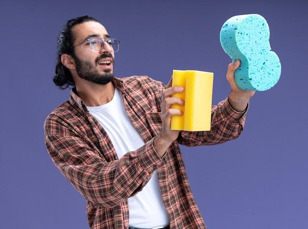 Glimlachende jonge knappe schoonmaakster die t-shirt draagt die sponzen aan kant standhoudt die op blauwe muur wordt geïsoleerd
