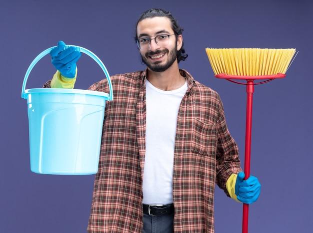 Glimlachende jonge knappe schoonmaakster die t-shirt en handschoenen draagt die emmer met zwabber houden die op blauwe muur wordt geïsoleerd