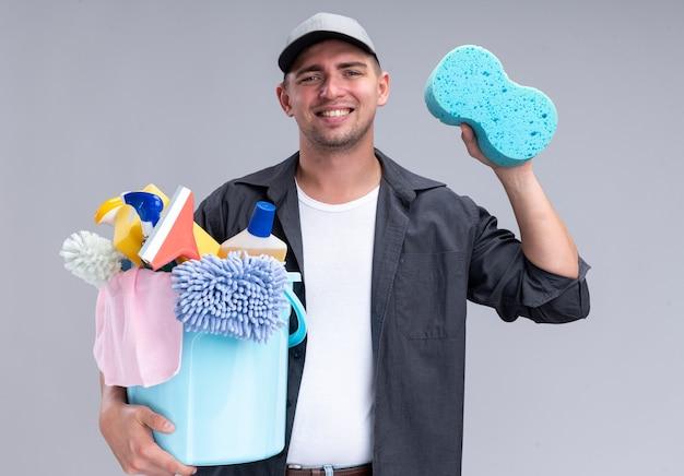Glimlachende jonge knappe schoonmaakster die t-shirt en pet draagt ?? die emmer met het schoonmaken van hulpmiddelen en spons houdt die op witte muur wordt geïsoleerd