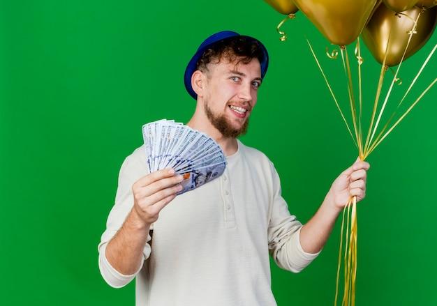Glimlachende jonge knappe slavische partijkerel die partijhoed draagt die ballons en geld bekijkt die camera bekijken die op groene achtergrond met exemplaarruimte wordt geïsoleerd