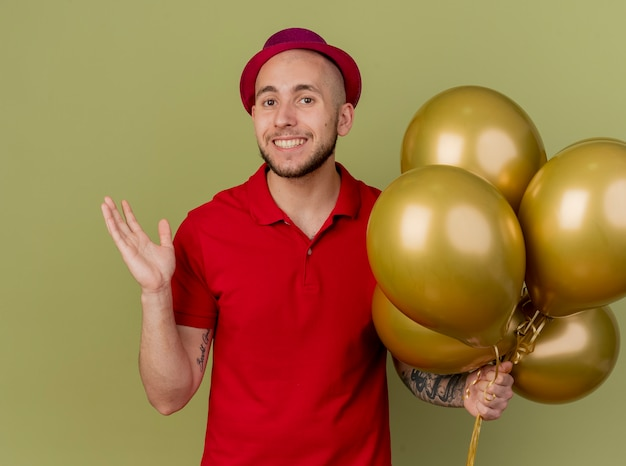 Glimlachende jonge knappe slavische partijkerel die partijhoed draagt ?? die ballons houdt die camera bekijkt die lege die hand op olijfgroene achtergrond toont