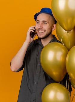 Glimlachende jonge knappe slavische partijkerel die partijhoed draagt die ballons houdt die over telefoon spreekt die recht op oranje achtergrond kijkt