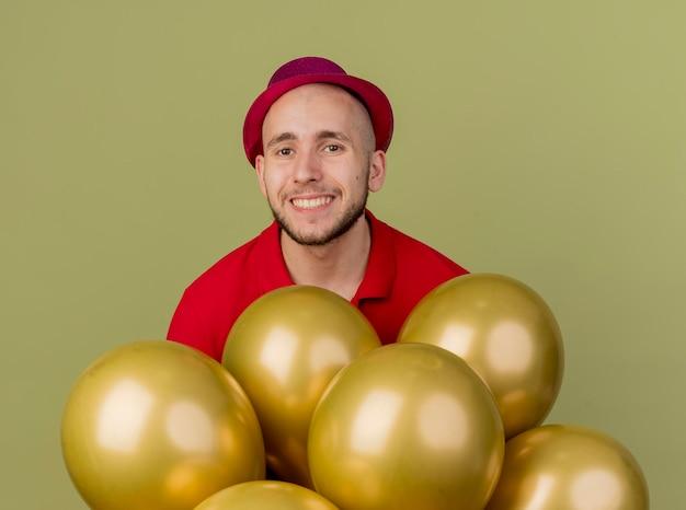 Glimlachende jonge knappe slavische partijkerel die partijhoed draagt die zich achter ballons bevindt die voorzijde bekijken die op olijfgroene muur wordt geïsoleerd