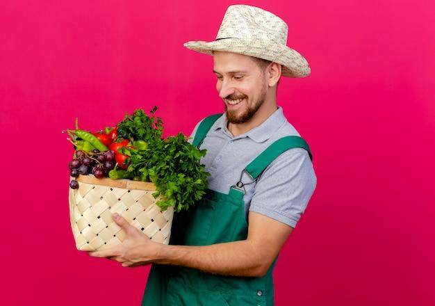 Glimlachende jonge knappe slavische tuinman in uniform en hoed houden en kijken naar mand met groenten