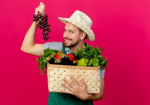 Glimlachende jonge knappe slavische tuinman in uniform en hoed met mand met groenten en druivenmost geïsoleerd op karmozijnrode muur met kopie ruimte