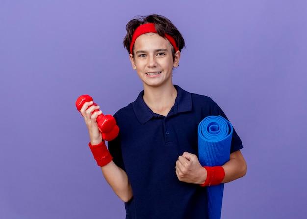 Glimlachende jonge knappe sportieve jongen die hoofdband en polsbandjes met beugels draagt die domoren en yogamat houden die op purpere muur met exemplaarruimte wordt geïsoleerd