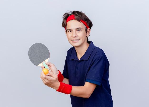 Glimlachende jonge knappe sportieve jongen die hoofdband en polsbandjes met beugels draagt die pingpongracket en bal houden die camera bekijkt die op witte achtergrond met exemplaarruimte wordt geïsoleerd