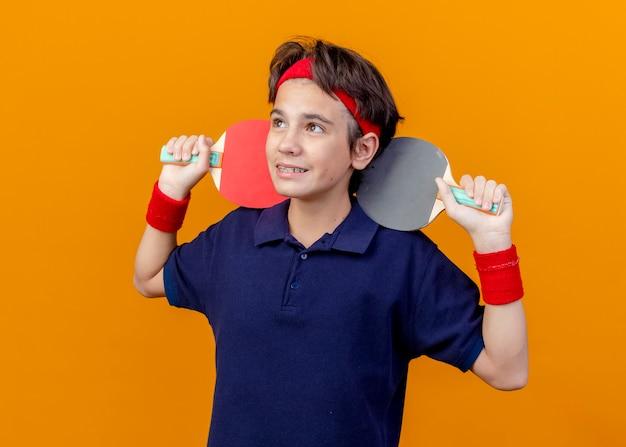 Glimlachende jonge knappe sportieve jongen die hoofdband en polsbandjes met beugels draagt die pingpongrackets op schouders houden die kant bekijken die op oranje achtergrond wordt geïsoleerd