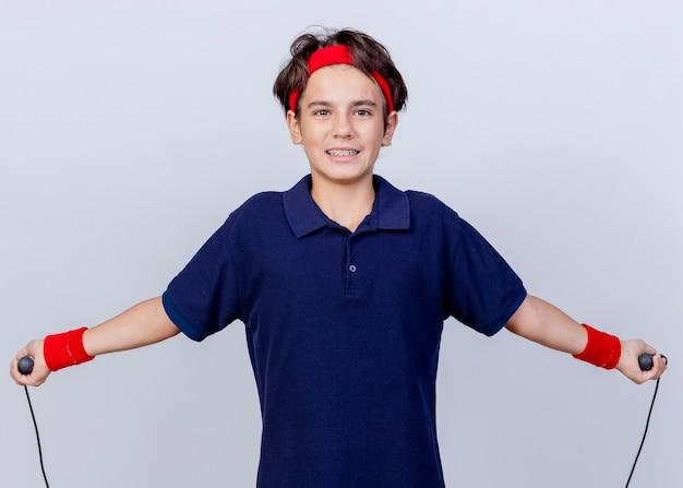 Glimlachende jonge knappe sportieve jongen die hoofdband en polsbandjes met tandsteunen draagt die camera springtouw bekijken die op witte achtergrond wordt geïsoleerd