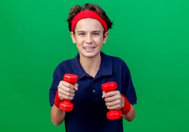Glimlachende jonge knappe sportieve jongen die hoofdband en polsbandjes met tandsteunen draagt die domoren houden die voorzijde bekijken die op groene muur met exemplaarruimte wordt geïsoleerd
