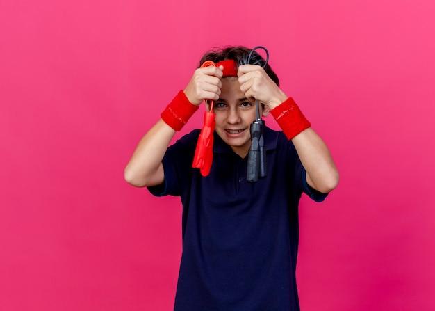 Glimlachende jonge knappe sportieve jongen die hoofdband en polsbandjes met tandsteunen draagt die springtouwen dichtbij gezicht houden die camera bekijken die op karmozijnrode achtergrond wordt geïsoleerd