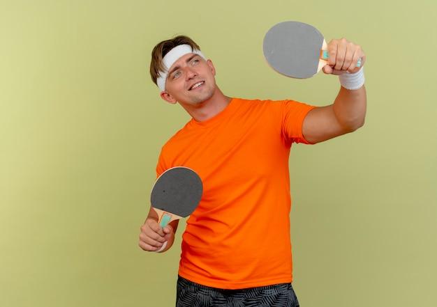 Glimlachende jonge knappe sportieve man met hoofdband en polsbandjes die pingpongrackets vasthouden en verhogen en kijken naar kant geïsoleerd op olijfgroene muur