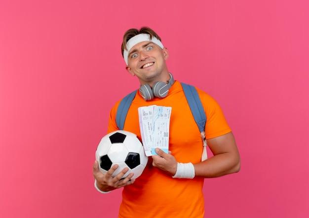 Glimlachende jonge knappe sportieve man met hoofdband en polsbandjes en rugtas met koptelefoon op de nek met vliegtuigkaartjes en voetbal geïsoleerd op roze muur