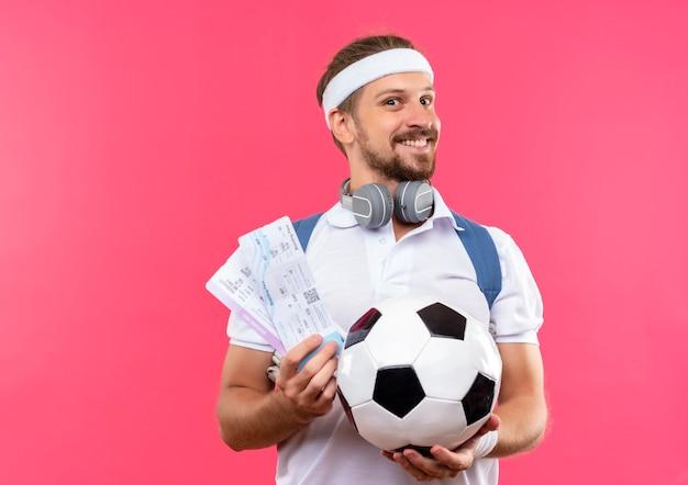 Glimlachende jonge knappe sportieve man met hoofdband en polsbandjes en rugtas met koptelefoon op nek houden voetbal en vliegtuigtickets geïsoleerd op roze ruimte