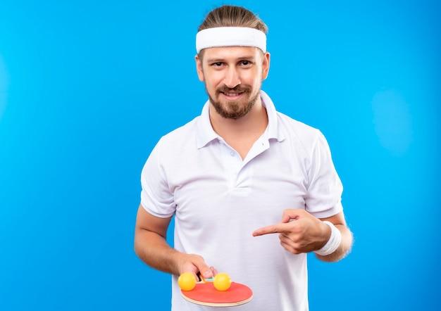 Glimlachende jonge knappe sportieve man met hoofdband en polsbandjes houden en wijzend op pingpongracket met ballen erop geïsoleerd op blauwe ruimte