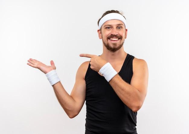 Glimlachende jonge knappe sportieve man met hoofdband en polsbandjes met lege hand en wijzend op het geïsoleerd op witte ruimte