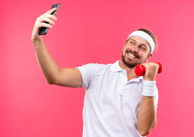 Glimlachende jonge knappe sportieve man met hoofdband en polsbandjes met mobiele telefoon en halter en kijken naar telefoon geïsoleerd op roze ruimte