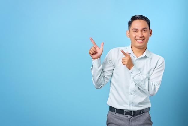 Glimlachende jonge knappe zakenman wijzende vinger weg naar kopieerruimte op blauwe achtergrond