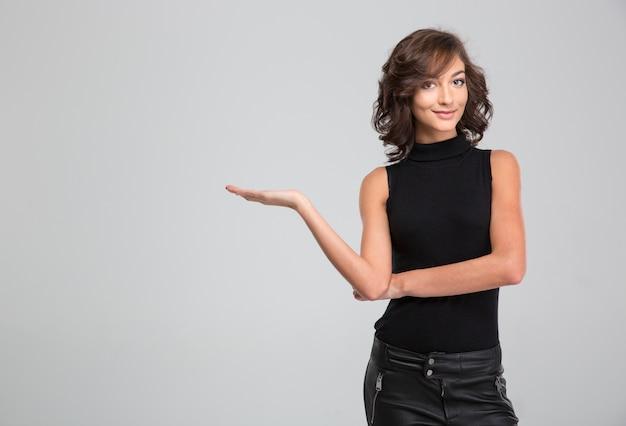 Glimlachende jonge krullende aantrekkelijke mooie vrouw die copyspace op de palm over witte muur houdt