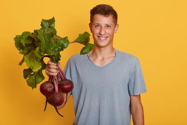 Glimlachende jonge landbouwer die met zijn oogst wordt gefotografeerd