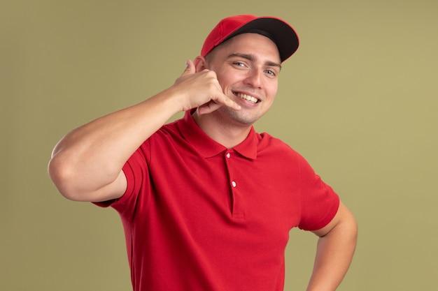 Glimlachende jonge leveringsmens die eenvormig en glb draagt die telefoongesprekgebaar tonen dat op olijfgroene muur wordt geïsoleerd