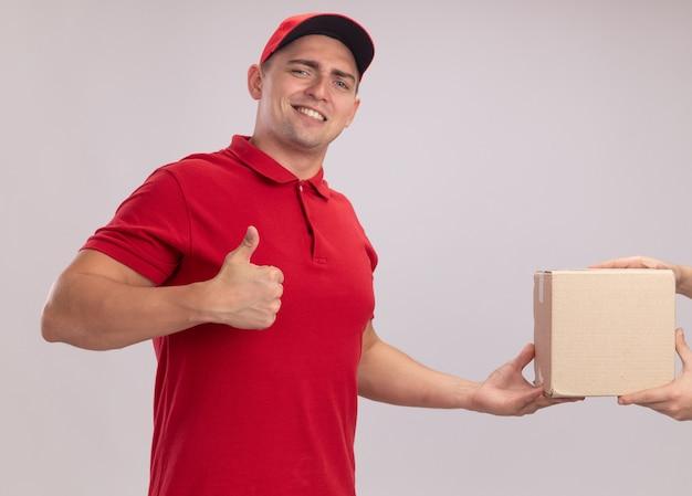 Glimlachende jonge leveringsmens die eenvormig met glb draagt die doos geeft aan cliënt die duim toont die omhoog op witte muur wordt geïsoleerd