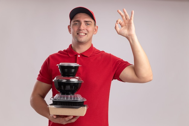 Glimlachende jonge leveringsmens die eenvormig met glb draagt die voedselcontainers houdt die ok gebaar tonen dat op witte muur wordt geïsoleerd