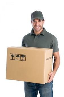Glimlachende jonge leveringsmens die en een kartondoos houdt die op witte achtergrond wordt geïsoleerd