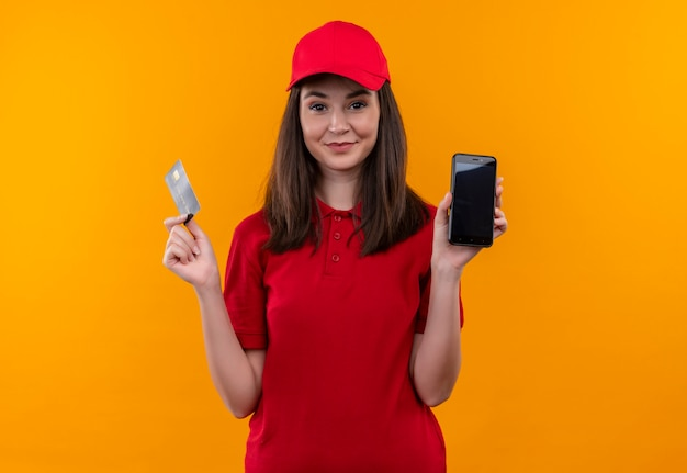 Glimlachende jonge leveringsvrouw die rode t-shirt in de rode kaart en de telefoon van de glbholding op geïsoleerde oranje muur draagt