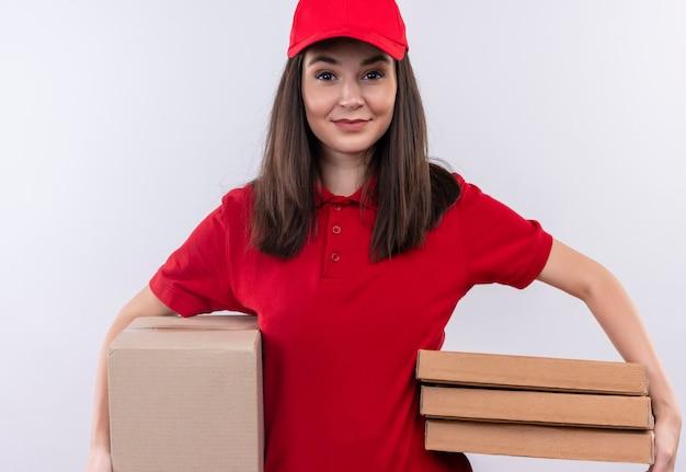 Glimlachende jonge leveringsvrouw die rode t-shirt in rode glb draagt die een doos en pizzadoos op geïsoleerde witte muur houdt